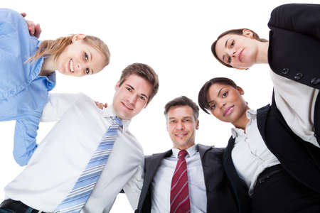 commitment: Group Of Businesspeople In A Circle Looking Down Over White Background