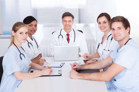 Happy Group Of Doctors Sitting In Meeting With Clipboard And Laptop photo