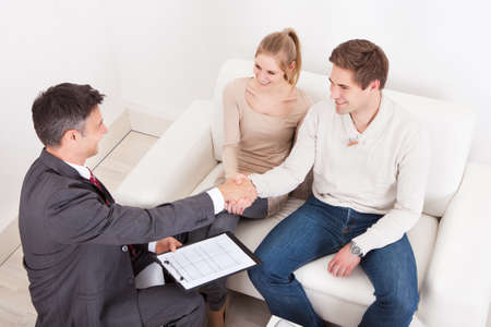 Male Consultant Shaking Hand With Young Couple At Home photo