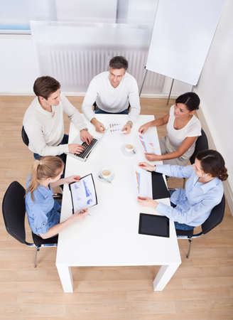 Group Of Businesspeople Discussing On Graph In Meeting photo