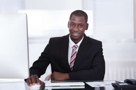 Happy Young African Businessman Using Computer At Desk Stock Photo - 25339788