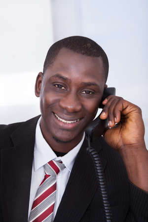 conference call: African Businessman Holding Receiver Talking On Telephone In Office