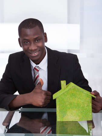 African Young Businessman Sitting At Office Presenting Ecological House photo