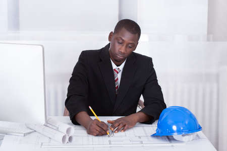 Happy Young Male African Architect Drawing Blueprint photo