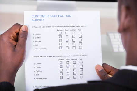 Close-up Of Businessman Filling Customer Survey Form photo