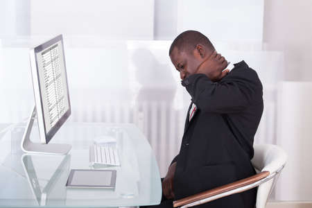 Young Businessman In Office At Desk Suffering From Neck Pain Stock Photo