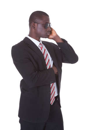 security company: Portrait Of An African Young Man In Suit Wearing Sunglasses Over White Background