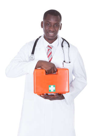 Young Male African Doctor Holding First Aid Box Over White Background photo