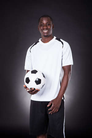 placer: Portrait Of A Happy Soccer Placer Holding Football Over Black Background