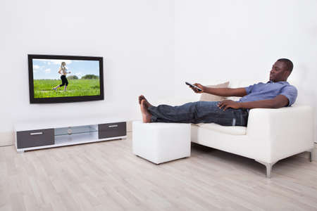 cable TV: African Man Sitting On Sofa With Remote Holding In Hand