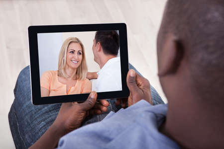 Close-up Of African Man Watching Video On Digital Tablet photo