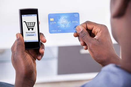 orden de compra: Close-up De La Persona tarjeta de crédito de la explotación agrícola con el teléfono móvil que muestra Compras Símbolo Foto de archivo
