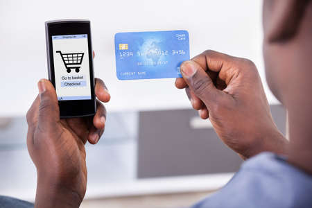 mobile shopping: Close-up Of Person Holding Credit Card With Mobile Phone Showing Shopping Cart Symbol Stock Photo