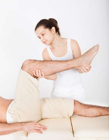 Young Man Lying On Table Getting Foot Massage From Masseuse Stock Photo - 25339875