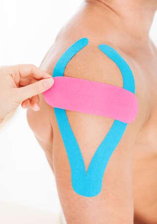 convulsion: Close-up De La Persona Solicitando Physio Especial Cinta sobre el hombro del hombre