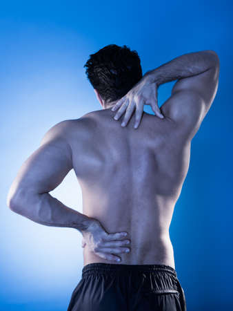 low back: Rear View Of Young Man Suffering From Back Pain Stock Photo