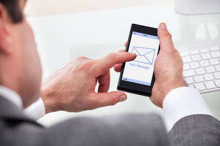new message: Close-up Of Businessman Holding Mobile With New Message On A Screen