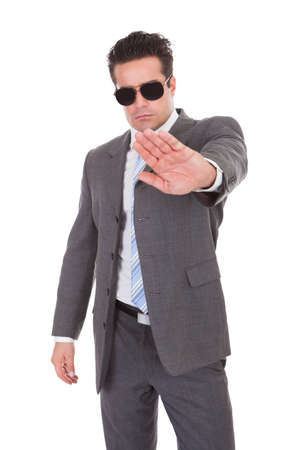 Portrait Of Young Businessman Wearing Sunglasses Gesturing Stop Sign photo