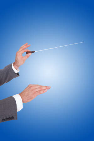 Close-up Of A Person Directing With A Conductors Baton On Blue Background photo