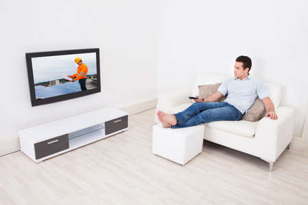 the footstool: Young Man At Home Watching News On Television