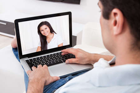 Close-up Of Young Man Having A Videochat With His Attractive Girlfriend photo