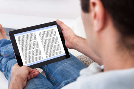 e book device: Close-up Of Man Holding Touch Screen Device Showing An E-book