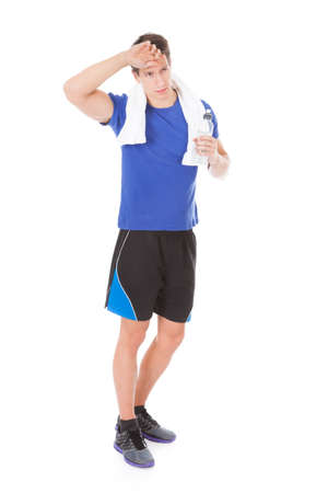 Portrait Of Tired Athlete Holding Water Bottle In Hand After Exercising photo