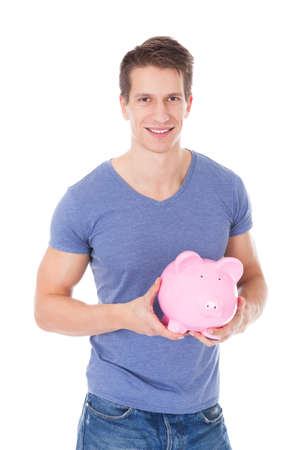 Portrait Of A Happy Young Man Holding Piggybank Over White Background photo