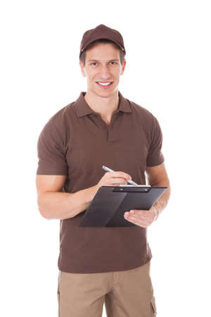 Young Delivery Man Writing On Clipboard Over White Background photo