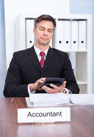 Portrait Of Mature Male Accountant Working At Office photo