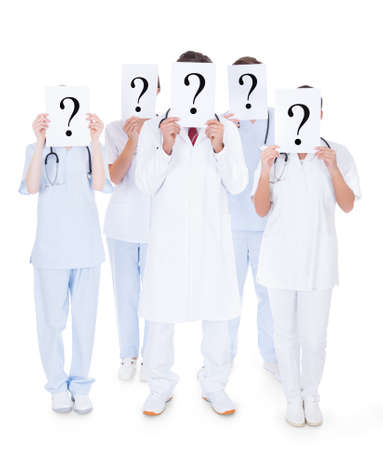 Group Of Doctors Hiding Face With Question Mark Sign Over White Background photo