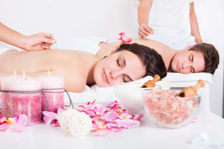 Relaxed Young Couple Receiving An Acupuncture Treatment In A Spa Center photo