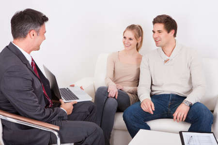 Consultant Advising Young Couple Sitting On Couch At Home photo