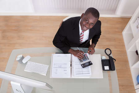 Young African Businessman Calculating Finance Bills With Calculator photo