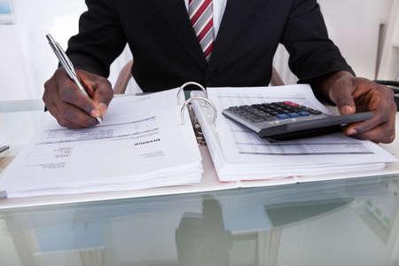 contabilidad financiera: Primer plano de un empresario africano Haciendo Cálculos Usando la calculadora Foto de archivo