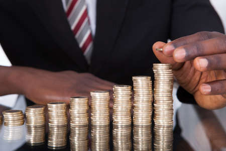 Close-up Of A Young African Businessman Stacking Coins On Desk
