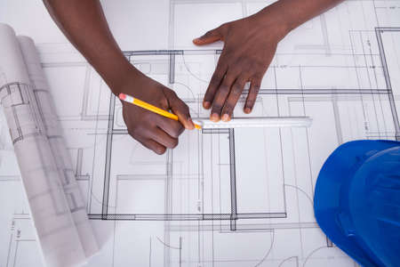 building plans: Close-up Of An African Draftsmans Hand Drawing Blueprint Stock Photo