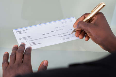 Close-up Of A Businessman Filling Blank Cheque photo