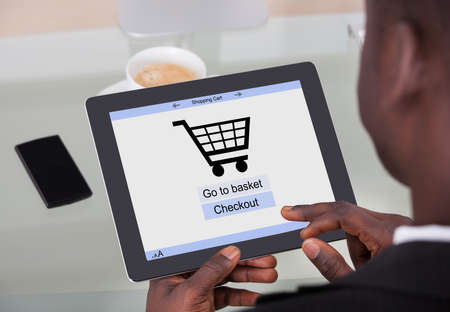 African Businessman Holding Digital Tablet With Online Shopping Application On A Screen photo
