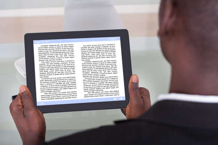 electronic book: Close-up Of An African Businessman Reading Story On Digital Tablet