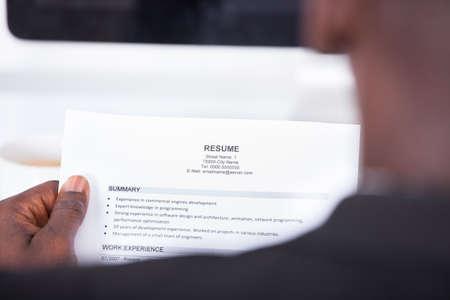 hombre escribiendo: Primer plano de un hombre de negocios mirando Resume sosteniendo en la mano Foto de archivo