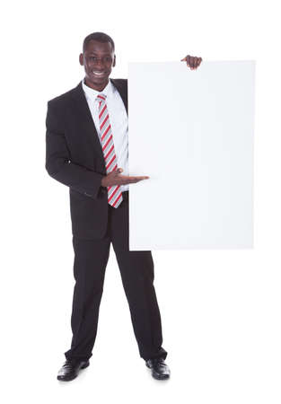 Portrait Of An African Businessman Presenting Blank Placard photo