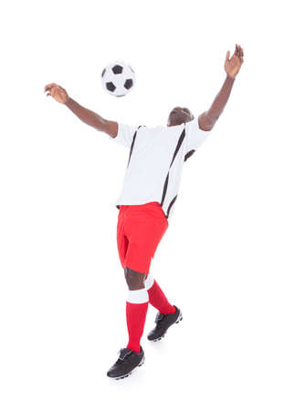 football socks: Happy African Player Playing With Soccer Ball Over White Background