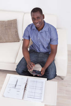 personal finance: Happy African Man Sitting On Couch Calculating Budget