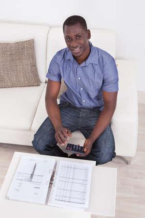 Hombre africano sentado en el sofá Calcular Presupuesto