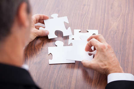 Portrait Of A Mature Businessman Solving Jigsaw Puzzle In Office photo