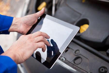 Close-up van een auto monteur met behulp van Digital Tablet