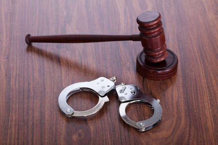 Photo Of Gavel And Handcuffs On Wooden Table photo