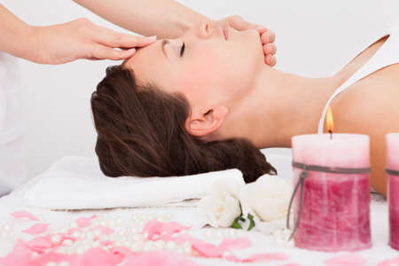 Young Woman With Eyes Closed Getting Massage Treatment From Masseuse Stock Photo - 25340098