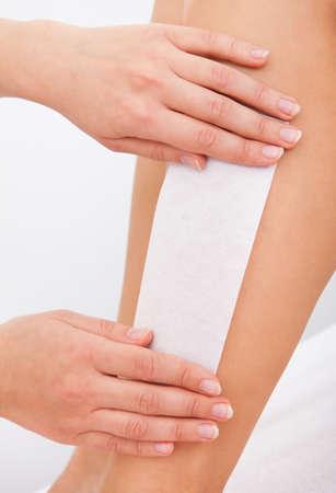 Beautician Waxing A Woman's Leg Applying Wax Strip Stock Photo - 25340101